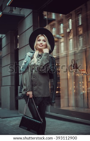 Young beautiful girl with perfect make-up, red lips, wearing a black  hat and leather coat, green shirt, posing near glass wall of the shopping center.