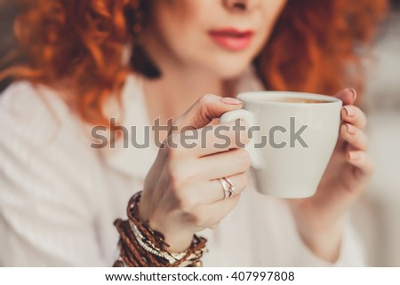 young beautiful girl with red hair in white dress posing sitting in a cafe the restaurant, Breakfast, lunch and dinner delicious fragrant drink hot coffee from a Cup,outdoor portrait, close up
