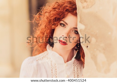 young beautiful girl with red hair posing outside the stone walls, beautiful eyes and soft skin, smile and white teeth, dressed in a retro jacket, a Sunny European city,outdoor portrait, close up - stock photo