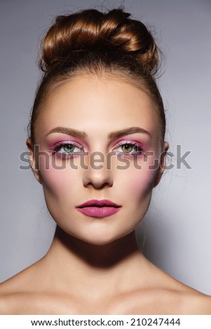 Young beautiful girl with stylish pink make-up and hair bun - stock photo