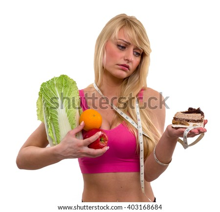 Young beautiful girl with tape measure holds fruits on her right hand and looks sadly at a piece of cake on her left hand, isolated over white background - stock photo