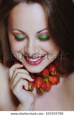 Young beautiful girl with white teeth enjoying strawberries, smiles and closed eyes
