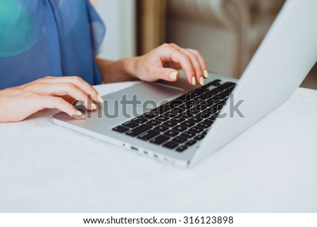 young beautiful girl working in the office on the laptop checks for new emails surf on the Internet