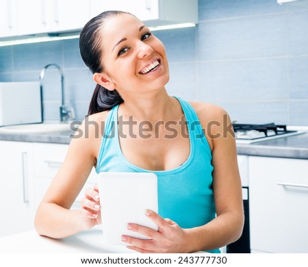 Young beautiful girl working with the tablet at home in the kitchen - stock photo