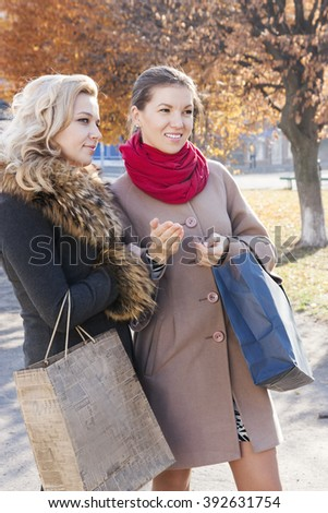 Young beautiful girlfriends with shopping bags on the city street - stock photo