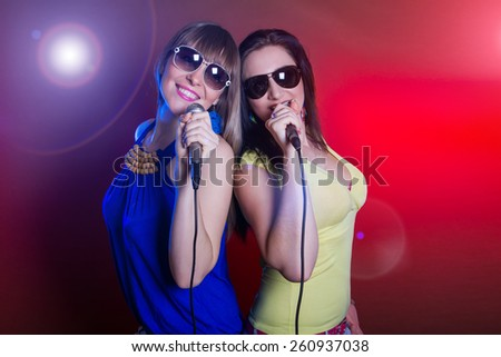 young beautiful girls dancing and singing - stock photo