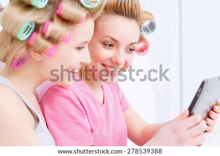 Young beautiful girls wearing pajamas and colorful hair rollers holding a tablet and smiling at home party in the light room - stock photo