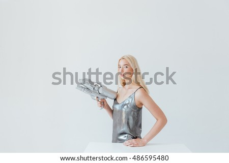 Young beautiful gorgeous woman in shiny silver dress with space blaster isolated on the grey background