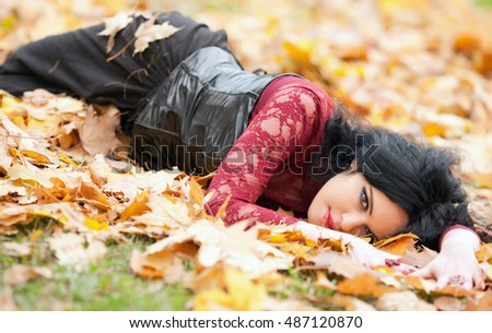Young beautiful gothic girl lying in autumn leaves