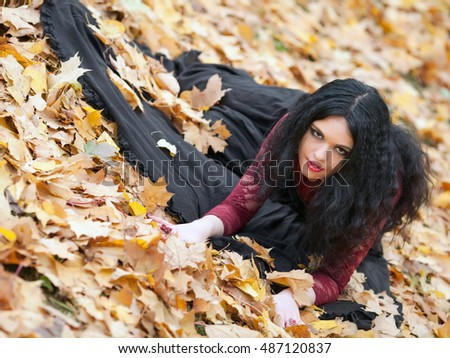 Young beautiful gothic girl sitting on the grass in the autumn leaves