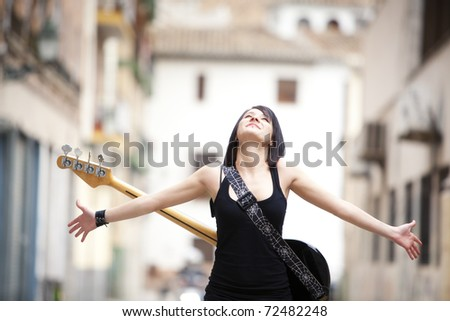 Young beautiful guitarist in urban background. - stock photo