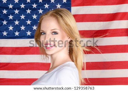 Young beautiful happy blonde woman posing against american flag at background