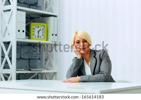 Young beautiful happy businesswoman sitting at the table in office