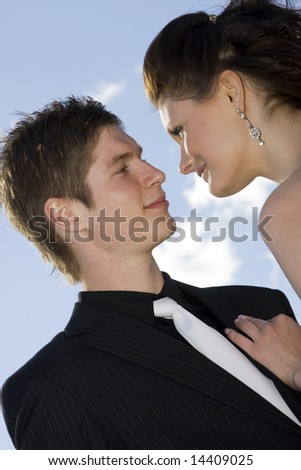 young beautiful happy couple on sky background