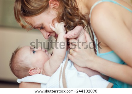 Young beautiful happy european mother holding newborn baby with blue eyes and playing with love and adore
