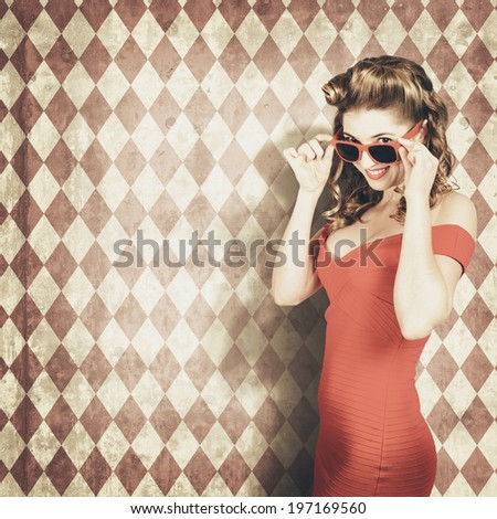 Young beautiful happy fashion woman peering over sunglasses on vintage summer background. Retro fashion pinup girls - stock photo