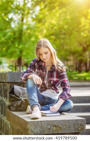 Young beautiful happy girl student sitting on the steps under the campus, university, school, education preparing to passing exam read the synopsis of the book in a notebook. Emotion - stock photo