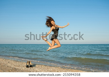 Young beautiful happy girl took off her shoes and jumping on the beach - stock photo