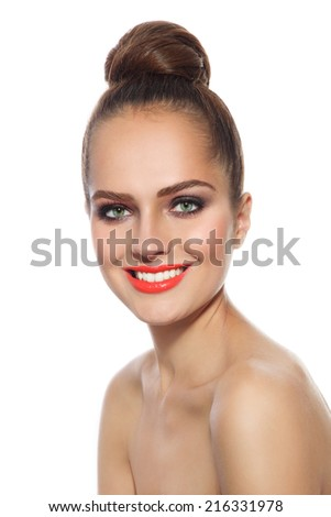 Young beautiful happy smiling girl with stylish make-up and hair bun over white background - stock photo