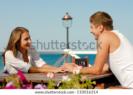 Young beautiful happy smiling romantic couple man and woman holding hands and sitting outdoors on cafe terrace on the bright windy summer day on a background of the blue sea and sky - stock photo