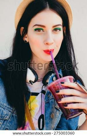young beautiful happy stylish hipster girl, cocktail, smoozy drink, denim jacket, smiling, fashion, teen, cool accessories, purse, hat, sunglasses, make-up, vintage style, wall background, headphones - stock photo
