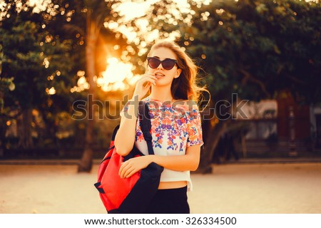 Young beautiful happy stylish hipster girl,cocktail,smoozy drink,denim jacket,smiling,fashion,teen,cool accessories,purse, hat,sunglasses,amazed,vintage style,sportive woman on the beach,hiker woman - stock photo