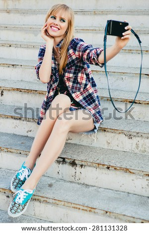 young beautiful happy stylish hipster girl, denim outfit, flirty happy, cool vintage style, having fun, sitting, stairs, oldschool film camera, take photo, hands holding, blond, smiling, making selfie - stock photo