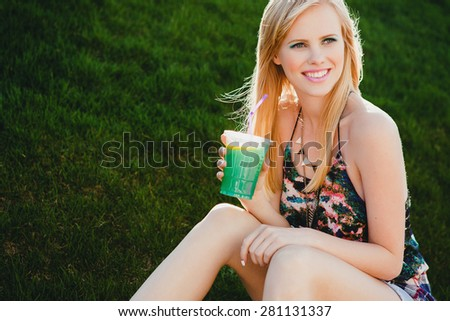 young beautiful happy stylish hipster girl with drink, smiling, sitting on grass in street, cool outfit, accessories, necklace, healthy, blond, copyspace, horizontal