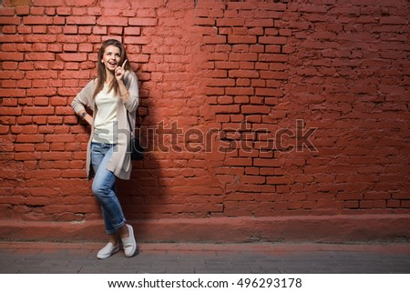 Young beautiful happy woman in casual cloths against brick wall