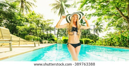 Young beautiful happy woman in hat and swimsiut in swimming pool. Tropical vacation.