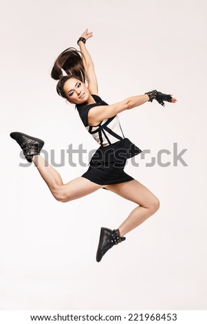 Young beautiful happy woman jumping against white background