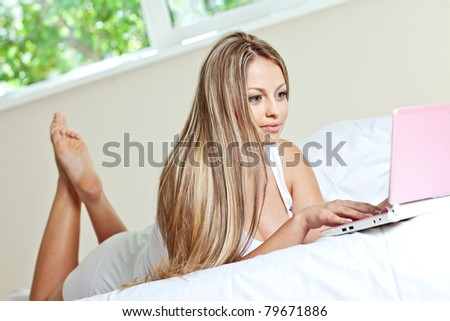 Young beautiful happy woman lying on the bed with laptop - stock photo