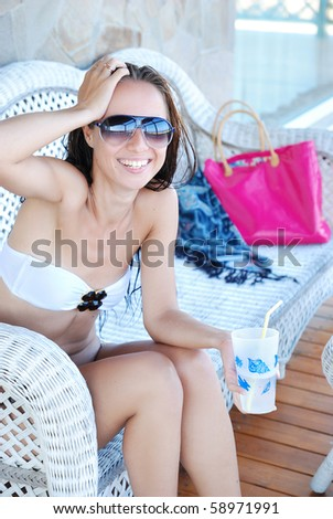 Young beautiful happy woman sitting on sofa on verandah