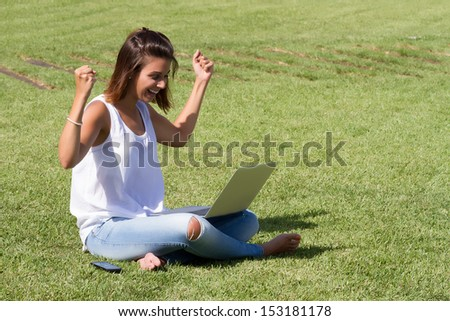 Young beautiful happy woman using laptop on campus/home yard in a sunny day.