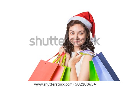 Young beautiful happy woman wearing Christmas hat holding shopping bags, on isolated white background with copy space
