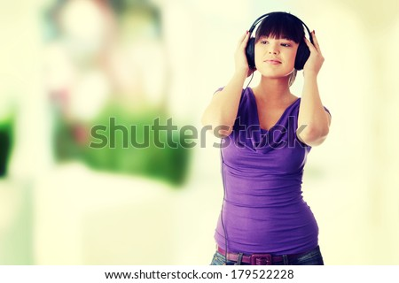 Young beautiful happy women listening music in headphones - stock photo