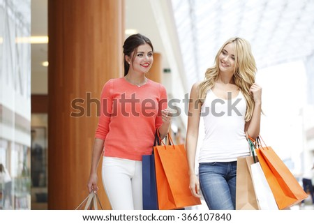 Young beautiful happy women with shopping bags in mall - stock photo