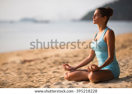 Young beautiful healthy woman making meditation on the beach, sunset on the sea. - stock photo