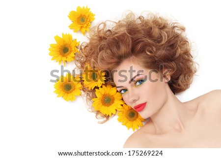 Young beautiful healthy woman with curly hair and sunflowers over white background - stock photo