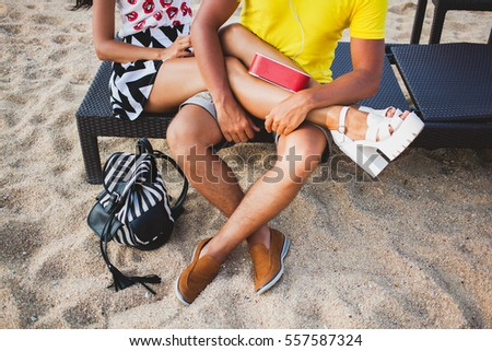 young beautiful hipster couple in love sitting on beach, listening to music, stylish outfit, summer vacation, colorful, skinny legs close up, backpack, shoes, tanned skin