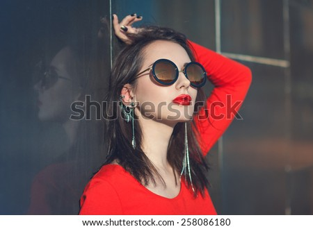 Young beautiful hipster girl in red blouse with sunglasses outdoor - stock photo