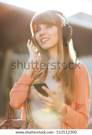 Young beautiful hipster girl listening to MP3 player on the street - stock photo