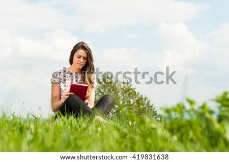 Young beautiful hipster sitting on meadow and reading a book with copy space - stock photo