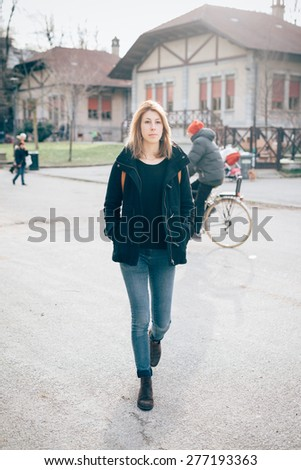 young beautiful hipster sporty blonde woman in town walking