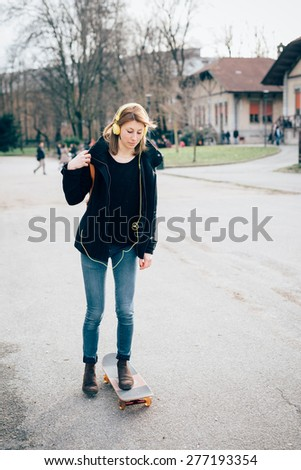 young beautiful hipster sporty blonde woman in town with skate bike and headphones
