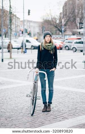 young beautiful hipster sporty blonde woman posing in the city holding her bike, looking in camera, hand in pocket, pensive - sportive, alternative methods of transportation concept - stock photo