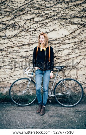 young beautiful hipster sporty blonde woman posing leaning against a wall with her bike, headphones around her chest and hand in pocket. Overlooking right. Music, sportive concept - stock photo