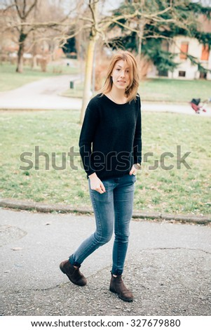 young beautiful hipster sporty blonde woman walking in a city park, hand in pocket, wearing blue jeans and black sweater, looking in camera, smiling - carefreeness, youth concept