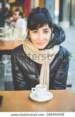 young beautiful hipster woman at the coffee bar in the city - stock photo