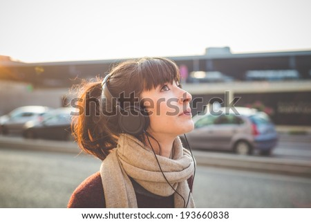 young beautiful hipster woman listening music with headphones in the city - stock photo